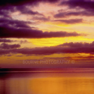 Purple and yellow clouds over calm, orange Sea of Cortez in Baja, Mexico at dusk.