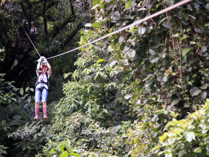 woman ziplining in the jungle